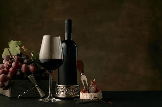 暗闇の中でワインボトル、チーズ、ワイングラスとブドウのおいしいフルーツプレートの正面図 無料写真