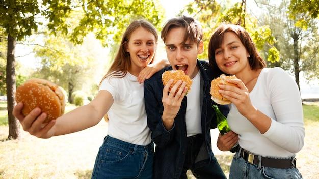 Вид спереди трех друзей в парке с пивом и гамбургерами Бесплатные Фотографии