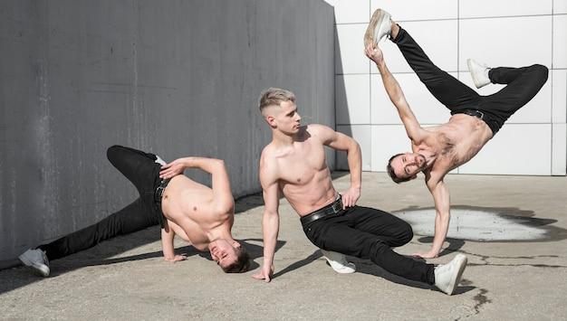 Вид спереди трех танцующих хип-хоп художников без рубашки Бесплатные Фотографии