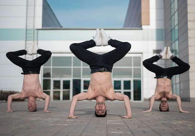 Вид спереди трех без рубашки танцоров хип-хопа, стоящих на их головах Бесплатные Фотографии