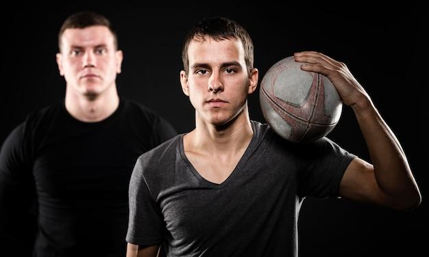 Вид спереди двух игроков в регби мужского пола, позирующих с мячом Бесплатные Фотографии