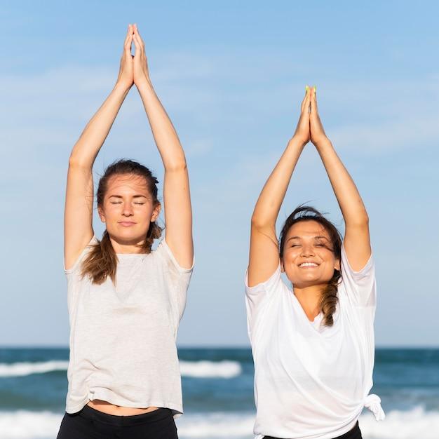 Вид спереди двух смайликов-подруг, тренирующихся вместе на пляже Premium Фотографии