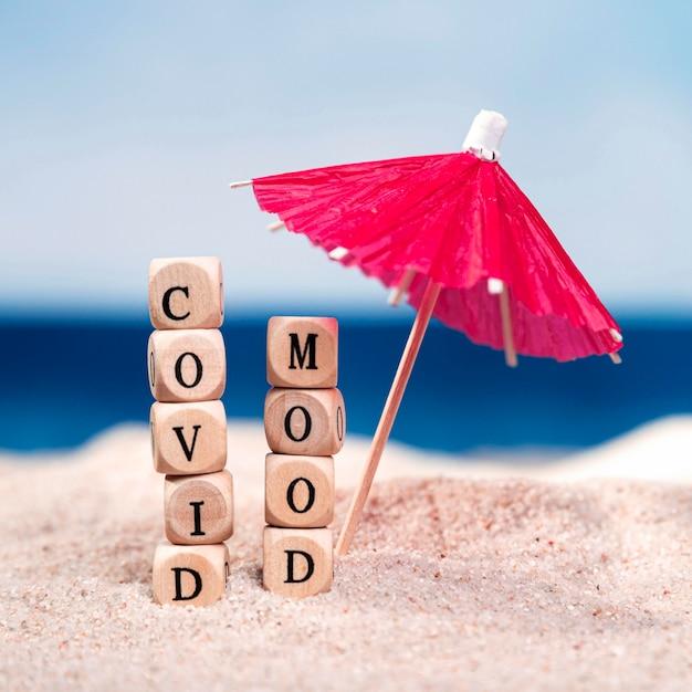 Covidムードとビーチで傘の正面図 無料写真