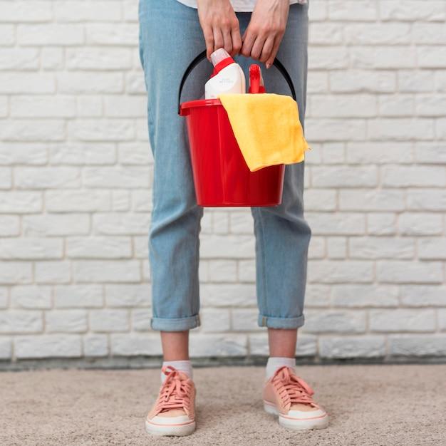 Вид спереди женщины, держащей ведро с моющими средствами Бесплатные Фотографии