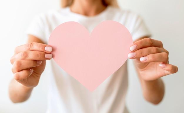 手で紙のハートを保持している女性の正面図 Premium写真