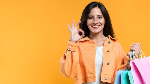 Вид спереди женщины, держащей хозяйственные сумки и делающей знак ок Premium Фотографии