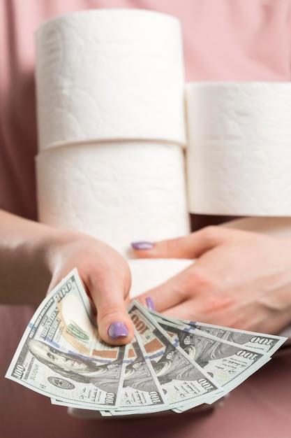 Вид спереди женщины, держащей рулоны туалетной бумаги и передачи денег Бесплатные Фотографии