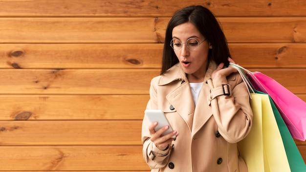 Вид спереди женщины, потрясенно смотрящей на свой телефон, держа сумки для покупок Бесплатные Фотографии