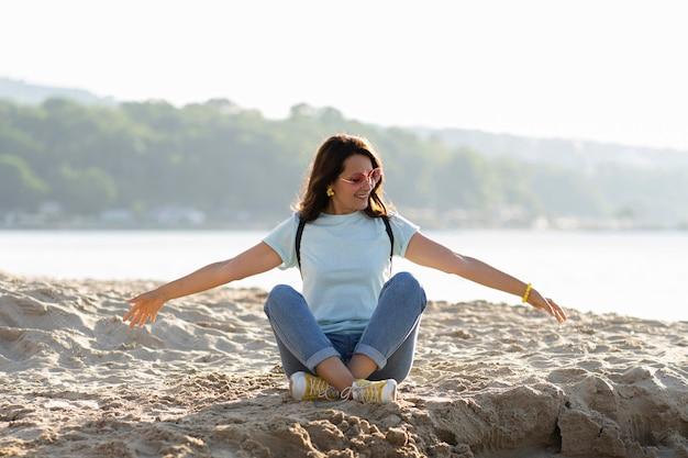 砂を楽しむビーチで女性の正面図 無料写真