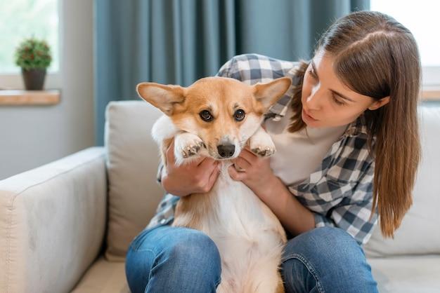 彼女の犬とソファの上の女性の正面図 無料写真