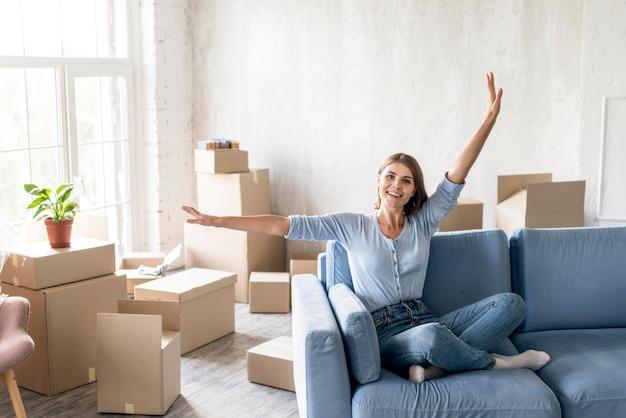 Вид спереди женщины на диване, довольной переездом Бесплатные Фотографии