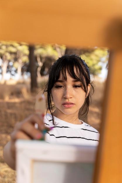 キャンバスに屋外で絵を描く女性の正面図 無料写真