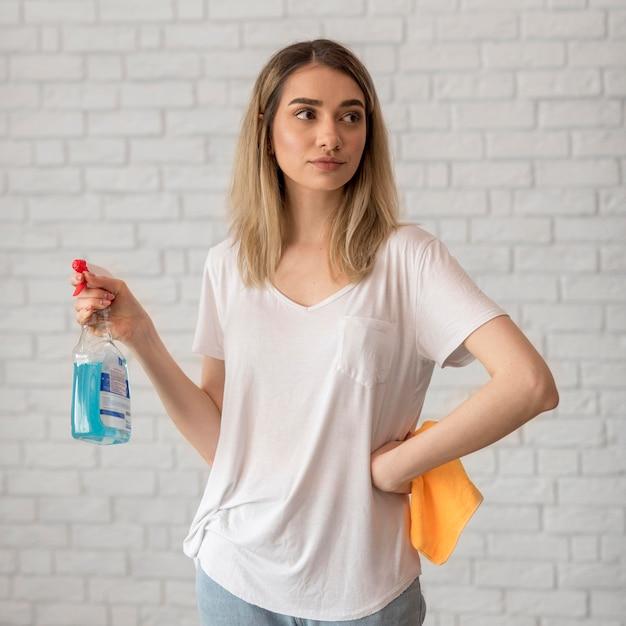 Вид спереди женщина позирует, держа чистящий раствор и ткань Бесплатные Фотографии