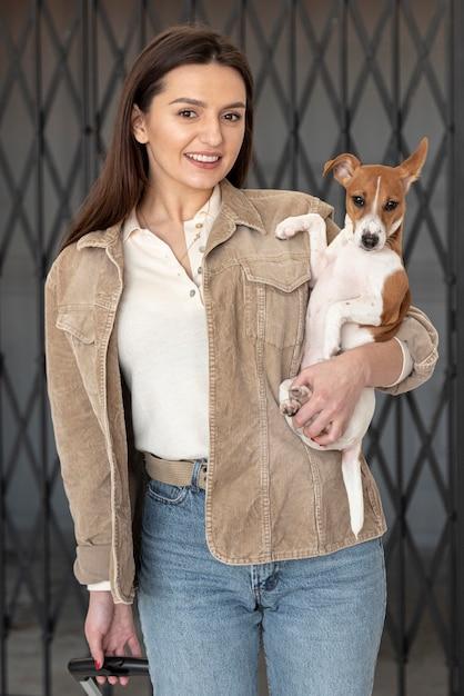 Вид спереди женщина позирует, держа ее собаку в руках Бесплатные Фотографии