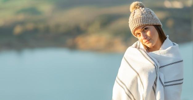 ロードトリップ中に毛布を着てポーズをとる女性の正面図 無料写真