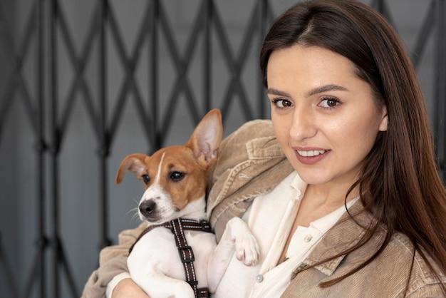 Вид спереди женщина позирует со своей собакой Бесплатные Фотографии