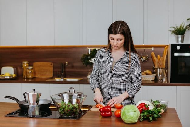 自宅のキッチンで食事を準備している女性の正面図 無料写真
