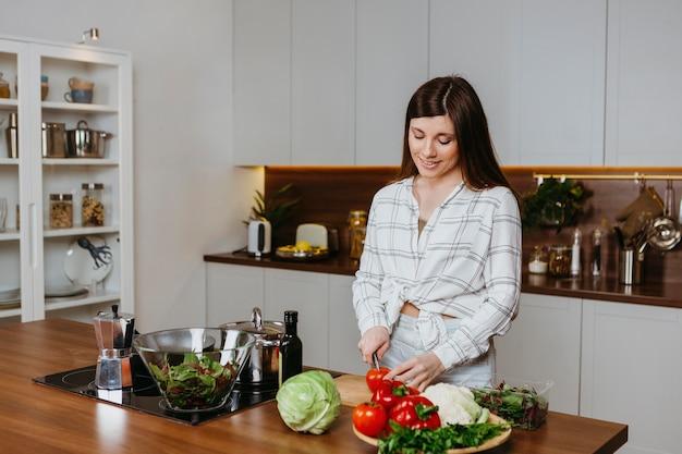 キッチンで食事を準備している女性の正面図 無料写真