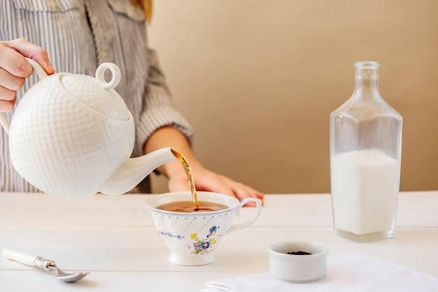 Вид спереди женщины готовит чай с молоком Premium Фотографии