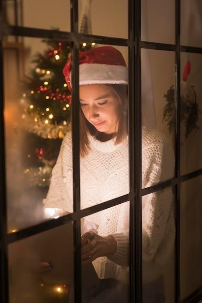 Вид спереди женщины через окно, глядя на планшет Бесплатные Фотографии