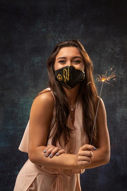 Вид спереди женщины в маске с фейерверком Бесплатные Фотографии