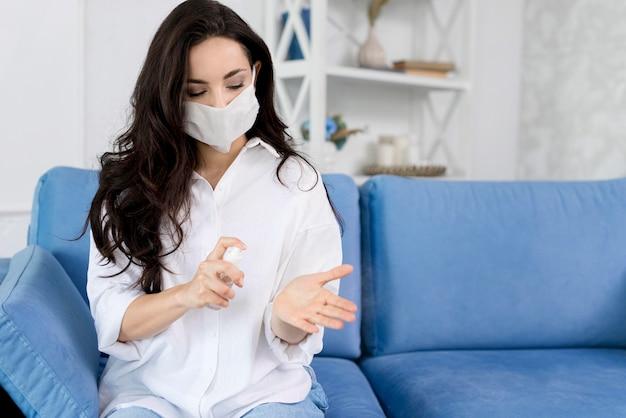 Вид спереди женщины с маской для лица, дезинфекция ее рук Premium Фотографии