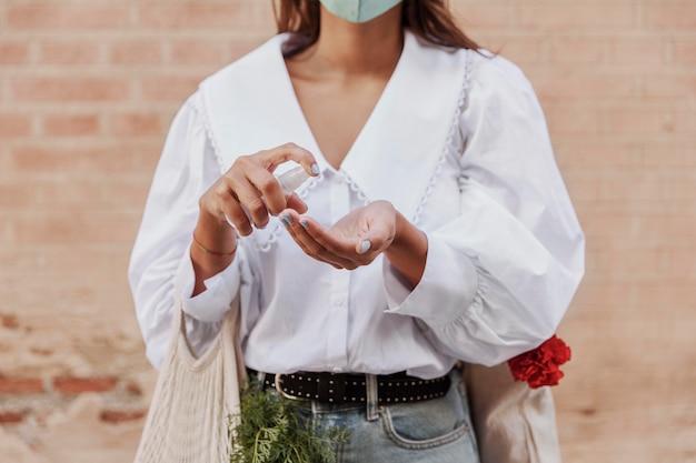 Вид спереди женщины с маской для лица, использующей дезинфицирующее средство для рук Бесплатные Фотографии