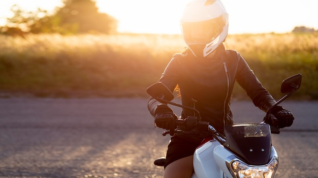 日没で彼女のバイクに乗ってヘルメットを持つ女性の正面図 無料写真