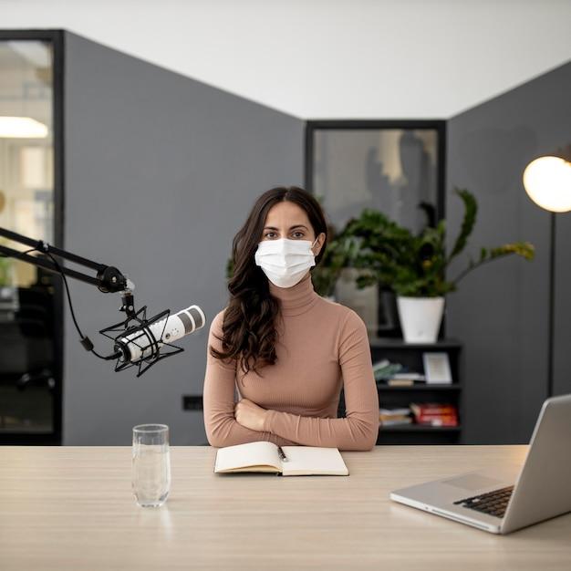 ラジオで放送されている医療マスクを持つ女性の正面図 無料写真