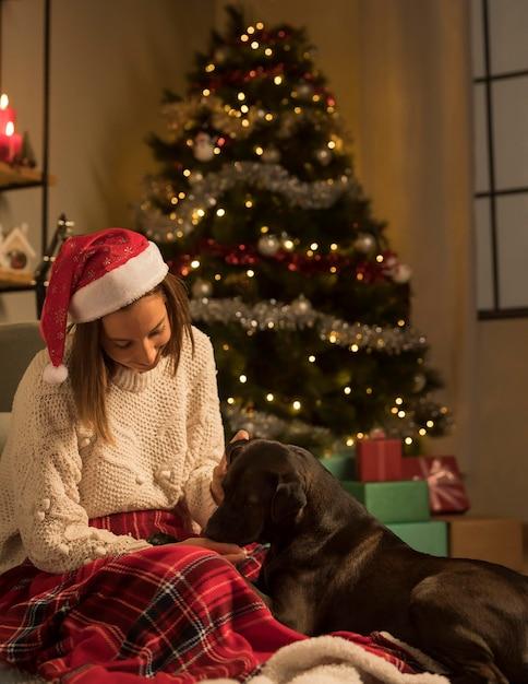 Вид спереди женщины в шляпе санта-клауса и ее собаки на рождество Бесплатные Фотографии