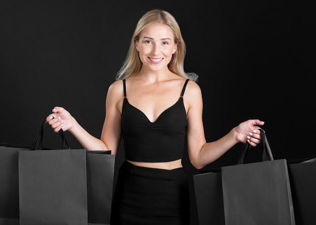 ショッピングバッグのコンセプトを持つ女性の正面図 無料写真