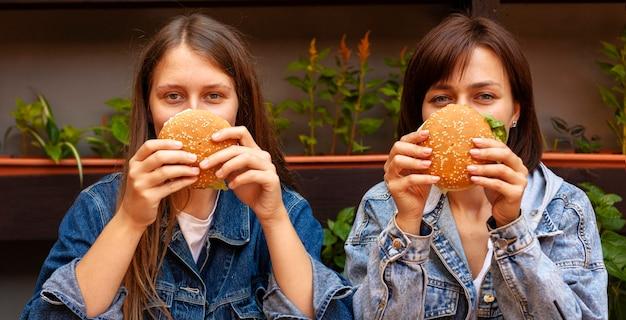 ハンバーガーで顔を覆っている女性の正面図 Premium写真