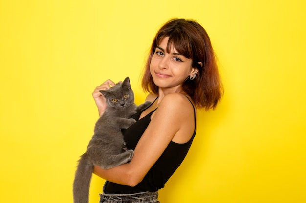 黄色の壁に灰色の子猫を保持している黒いシャツと灰色のジーンズの若い女性の正面図 無料写真