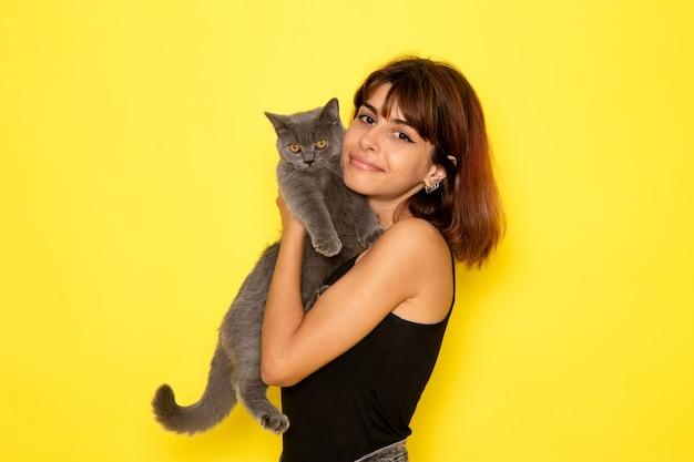 黄色の壁に子猫を保持して笑っている黒いシャツの若い女性の正面図 無料写真