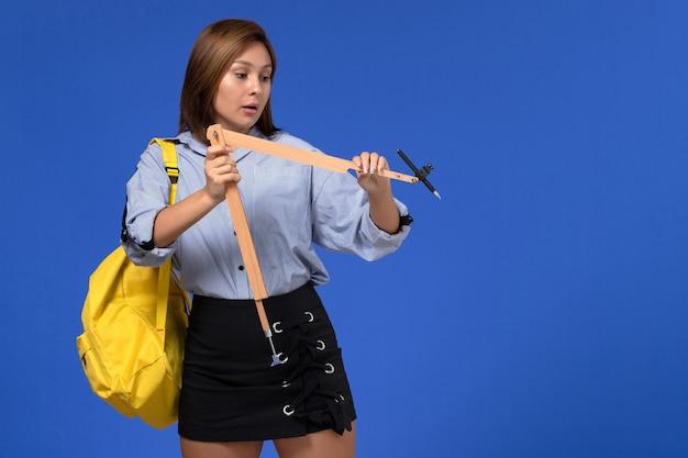 나무 삼각형 모양을 잡고 파란색 셔츠에 젊은 여성의 전면보기 무료 사진