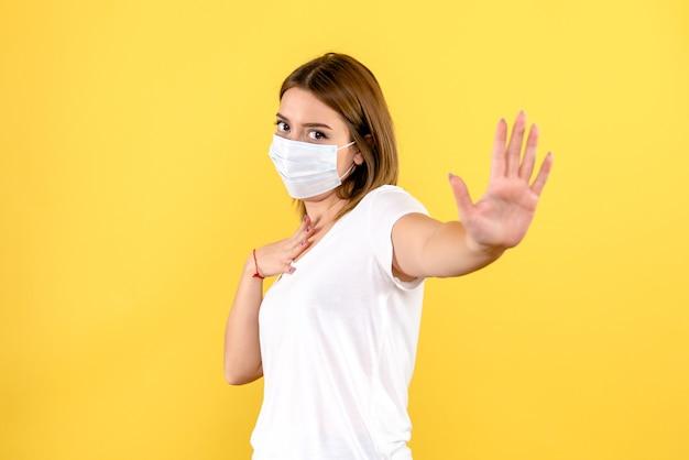 Вид спереди молодой женщины в маске на желтой стене Бесплатные Фотографии