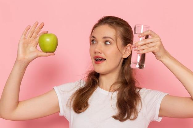 ピンクの壁に新鮮な青リンゴと水のガラスを保持している白いtシャツの若い女性の正面図 無料写真
