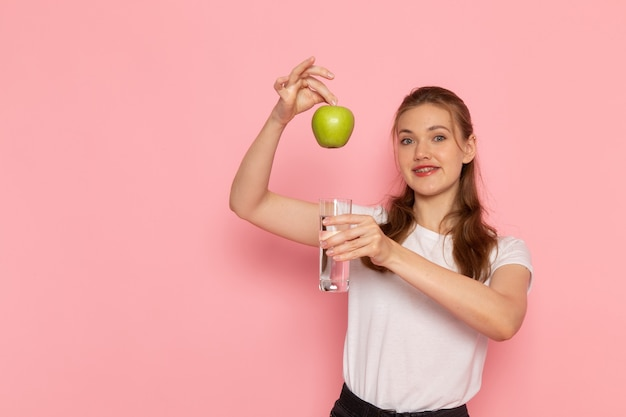 新鮮な青リンゴと水のガラスを保持している白いtシャツの若い女性の正面図 無料写真