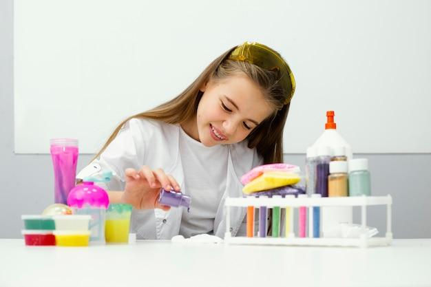 점액과 색상을 실험하는 어린 소녀 과학자의 전면보기 무료 사진