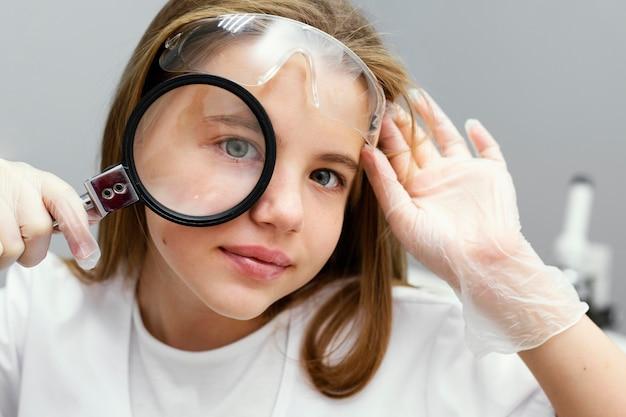 돋보기와 어린 소녀 과학자의 전면보기 무료 사진