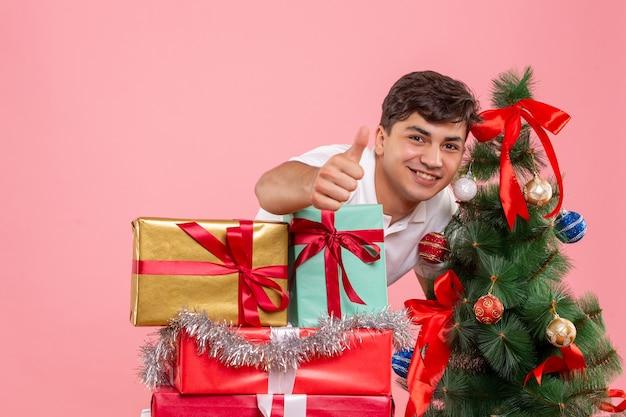 ピンクの壁にクリスマスプレゼントと休日の木の周りの若い男の正面図 無料写真