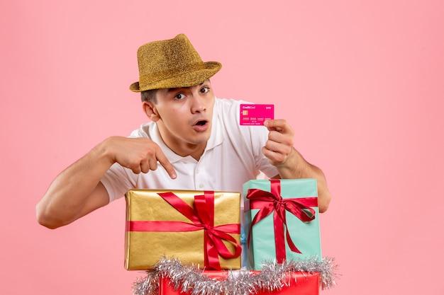 ピンクの壁に銀行カードを保持しているクリスマスプレゼントの周りの若い男の正面図 無料写真