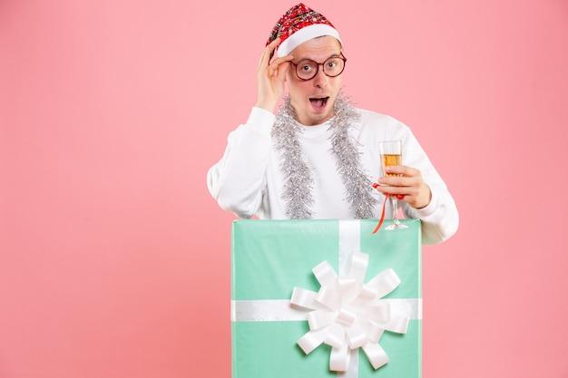 분홍색 벽에 음료와 화환으로 크리스마스를 축하하는 젊은 남자의 전면보기 무료 사진