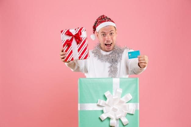 ピンクの壁にプレゼントと銀行カードを保持している若い男の正面図 無料写真