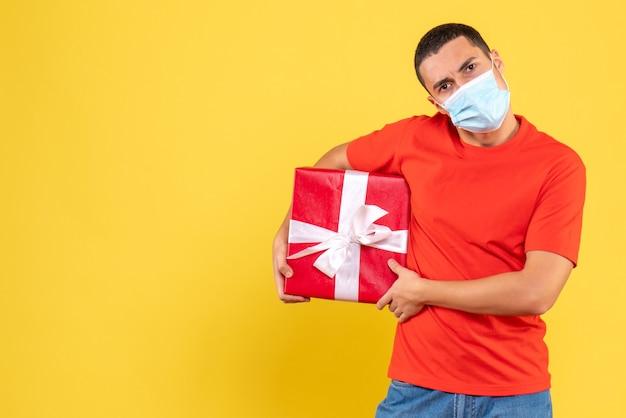 Вид спереди молодого человека, держащего в стерильной маске на желтой стене Бесплатные Фотографии