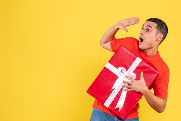 黄色の壁に驚きの表情でプレゼントを保持している若い男の正面図 無料写真