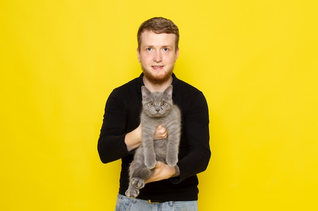 Вид спереди молодого человека в черной рубашке держит милый серый котенок с улыбкой Бесплатные Фотографии