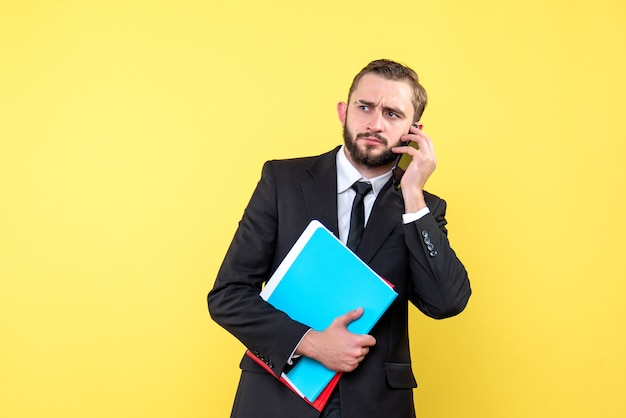 전화를 들고 노란색에 폴더를 들고 기다리고 검은 양복에 젊은 남자의 전면보기 무료 사진