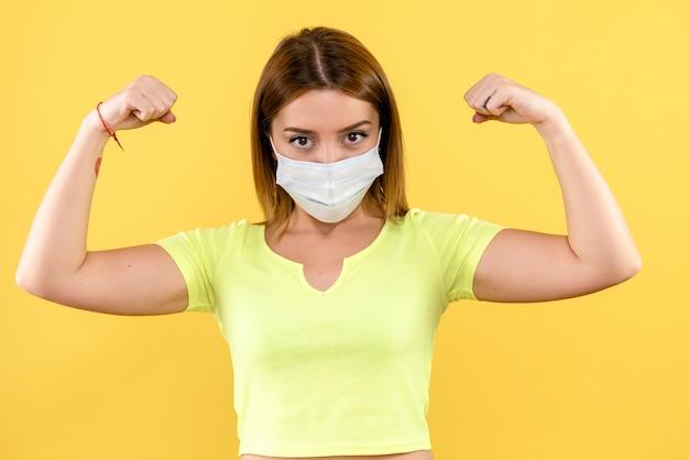 Вид спереди молодой женщины, изгибающейся в маске на желтой стене Бесплатные Фотографии