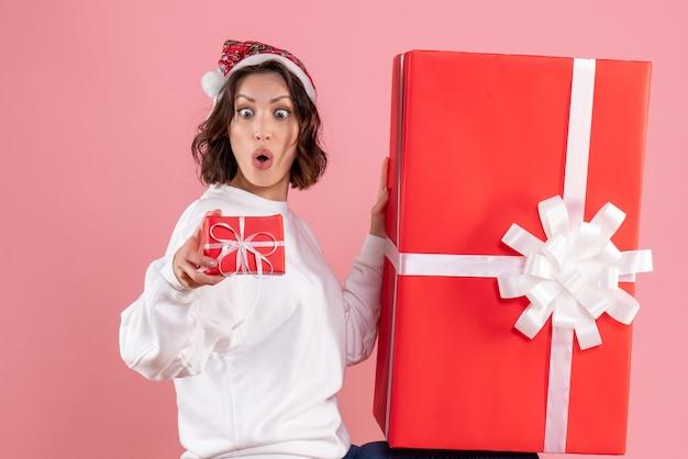 분홍색 벽에 거대한 하나 선물 작은 크리스마스를 들고 젊은 여자의 전면보기 무료 사진